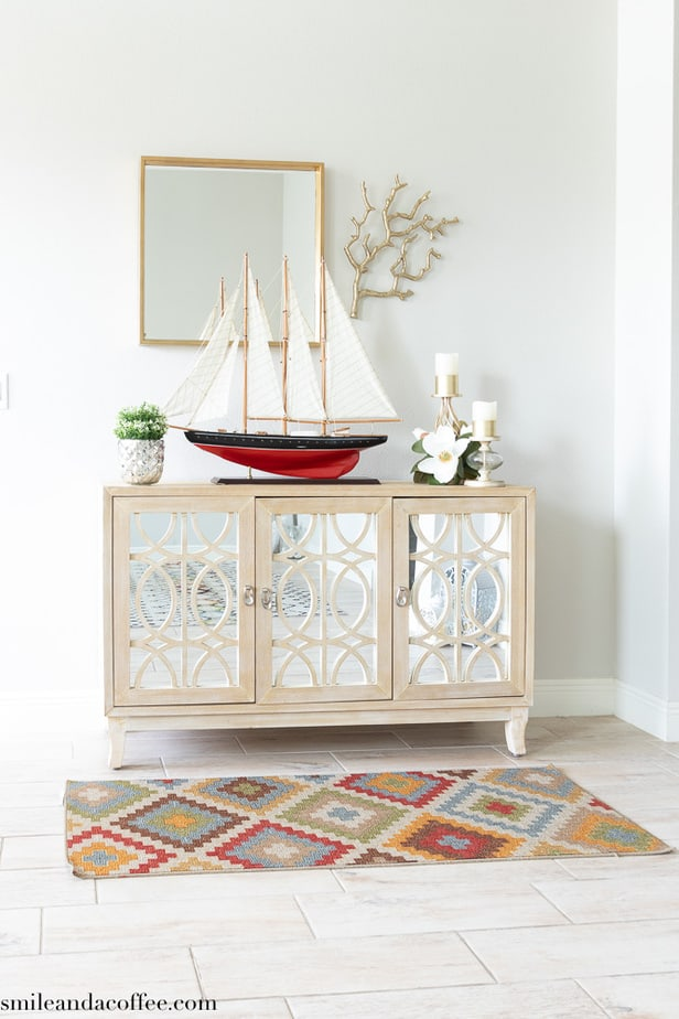 red and gold theme entryway with mirrored console, red sailboat , multicolored rug, gold candle stand and plant pot